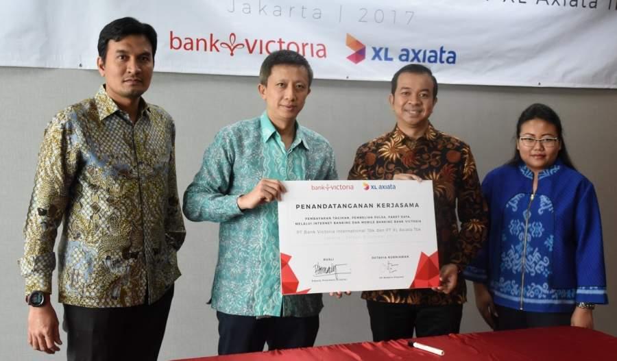 Wakil Direktur Utama / Deputy President Director PT Bank Victoria Internasional Tbk, Rusli ( kiri tengah ) bersama VP Modern Channel XL Axiata, Octavia Kurniawan ( kanan tengah ) menandatangani Perjanjian Kerjasama.